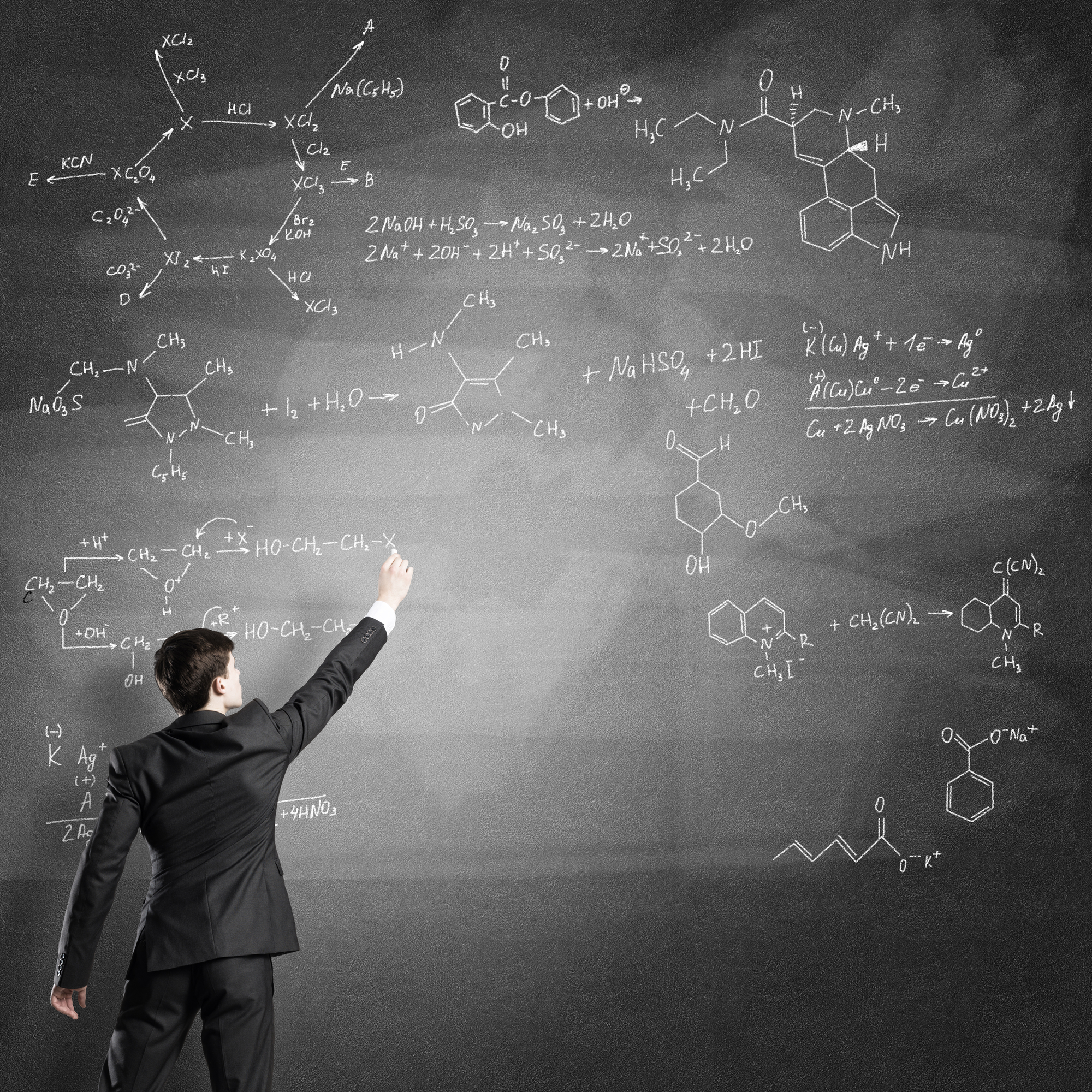 Young man in suit drawing chemistry formulas on chalkboard